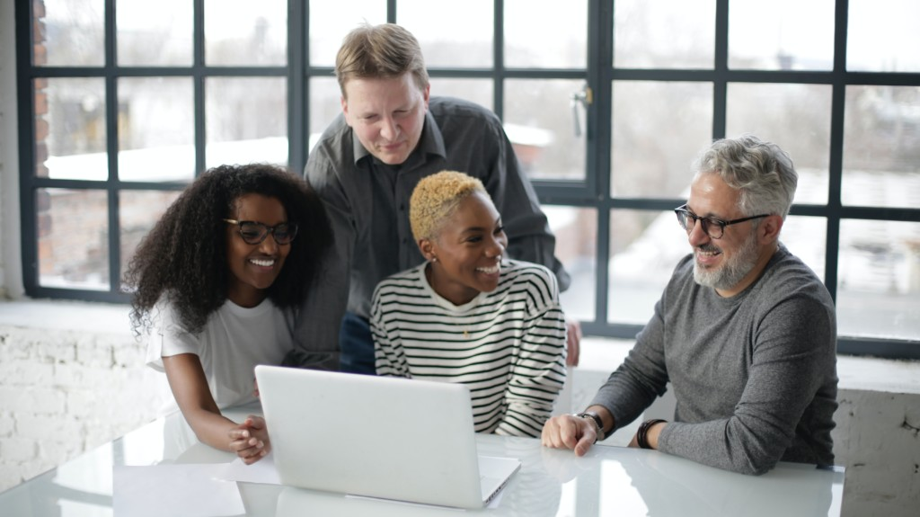 Multi-generational procurement team collaborating with technology